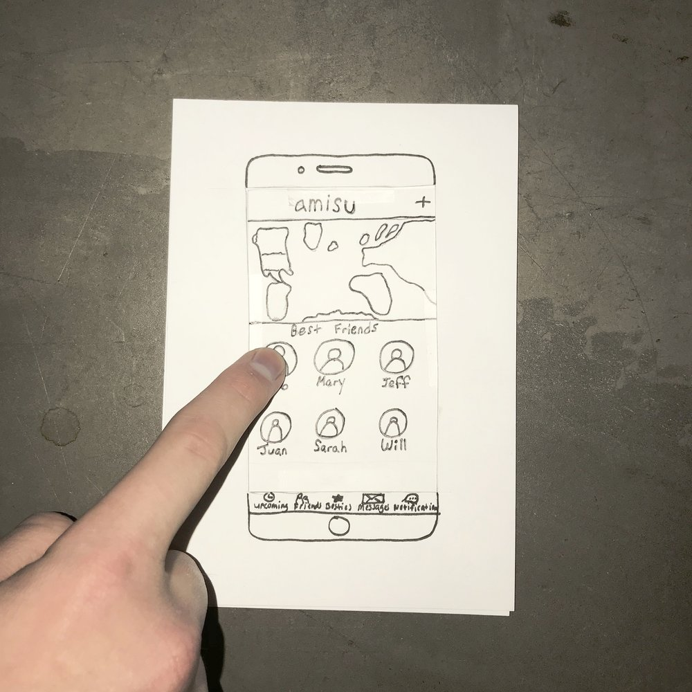 A finger taps on a paper prototype