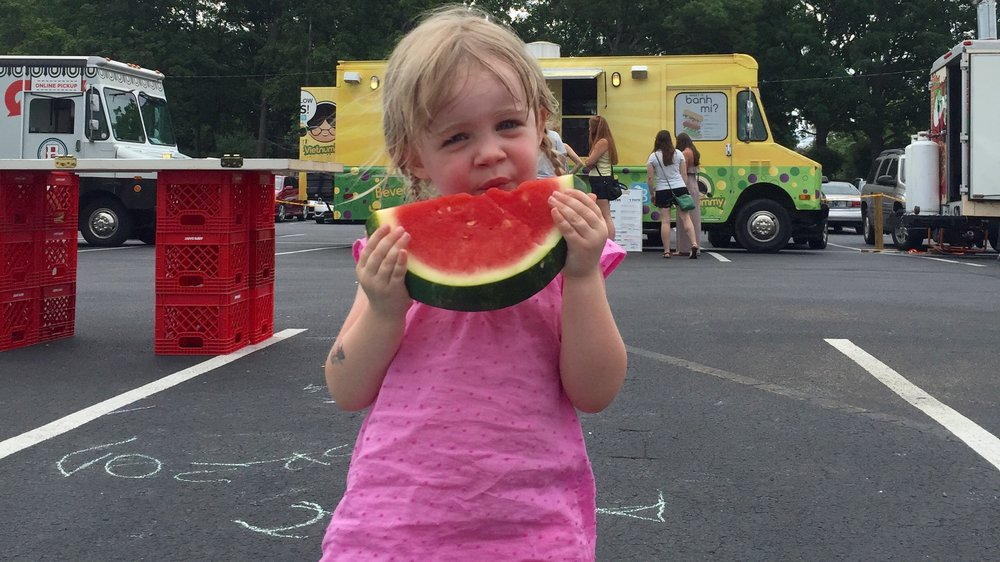 My daughter, Piper, enjoying some watermelon at the food truck rally at Ted's Market