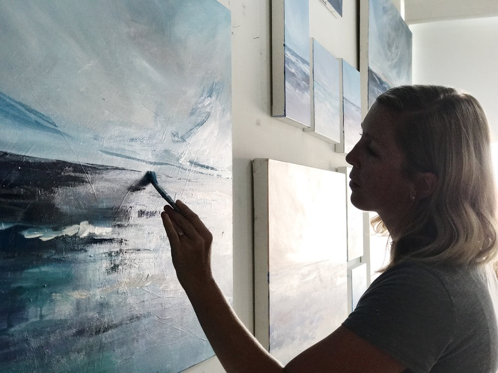 Megan Elizabeth painting an ocean in her studio in NYC