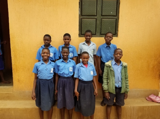 Some of our P7 students in front of one of their dorm rooms