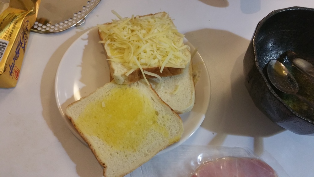 Melted butter spreaded all over the bread with cheese toppings.