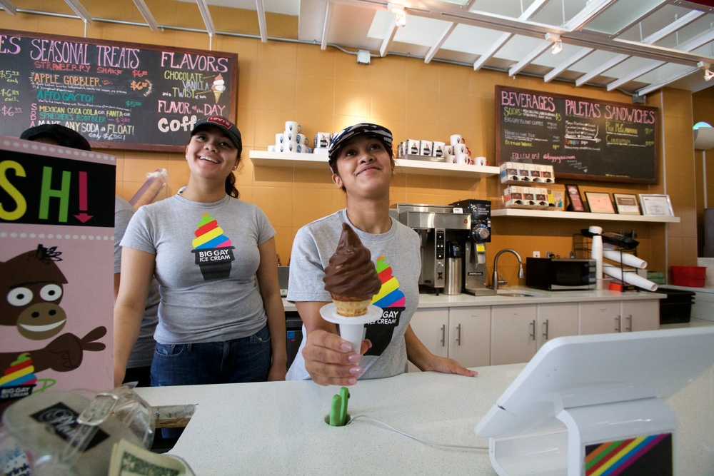 TWO SMILING YOUNG LADIES SERVING AN ICE CREAM CONE