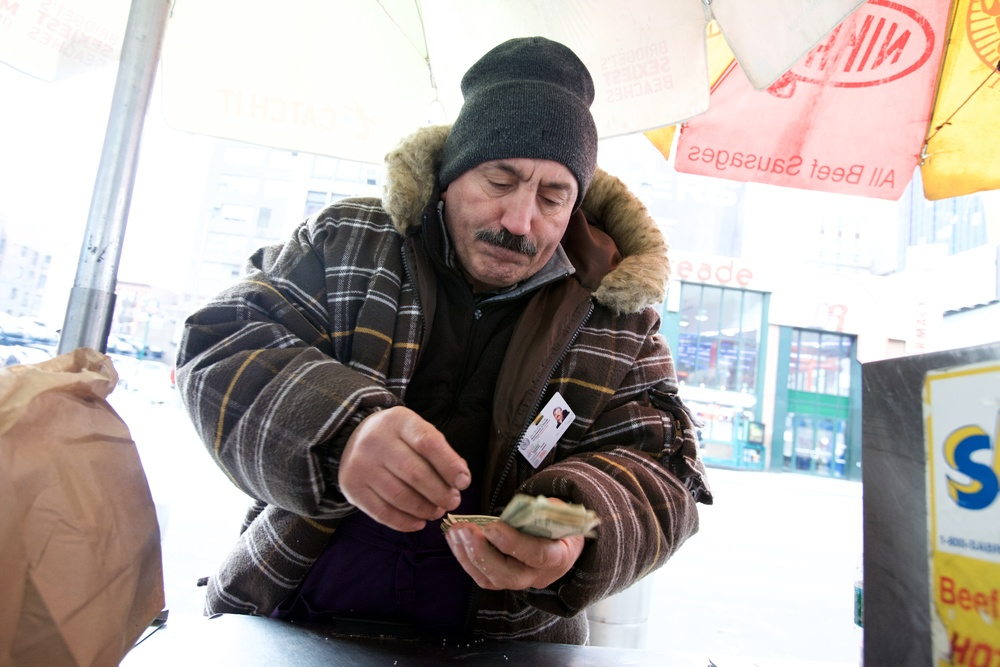 STREET VENDOR COUNTING THE CHANGE