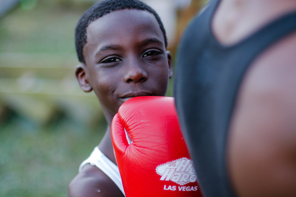 Kentrell Dantzler, 9, is a main member of the Running Bear Boxing Club, and also headed to compete in the Silver Gloves Tournament at the end of December 2015. Here, he looks away from a closing talk by Coach Ford. The coach has to get on his knees to spar with Kentrell, as he has no other younger members of the Lower Ninth to practice with.