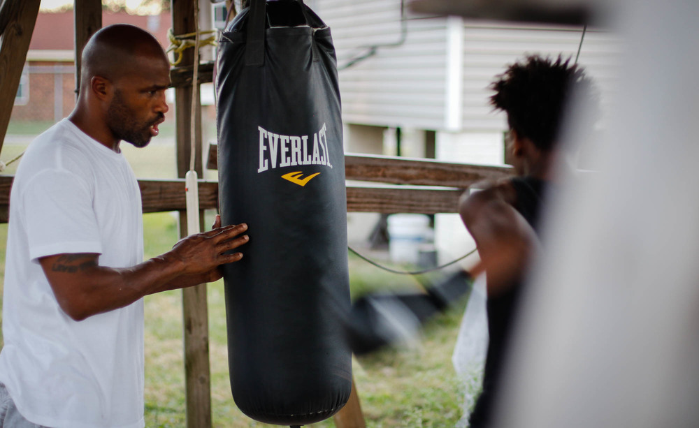 "Coach Darien Ford has 35 professional matches under his belt. His high, raspy voice rings out in the yard as the twins practice on the bags, huffing and hissing through their teeth with every punch. ""Hands up high, and bring that jab back. Use your speed. Float like a butterfly, that's what Muhammad Ali say. Sting like a bee. A butterfly ain't got no gravity, stay light on your feet. He smooth, he fast. Hands up high."""