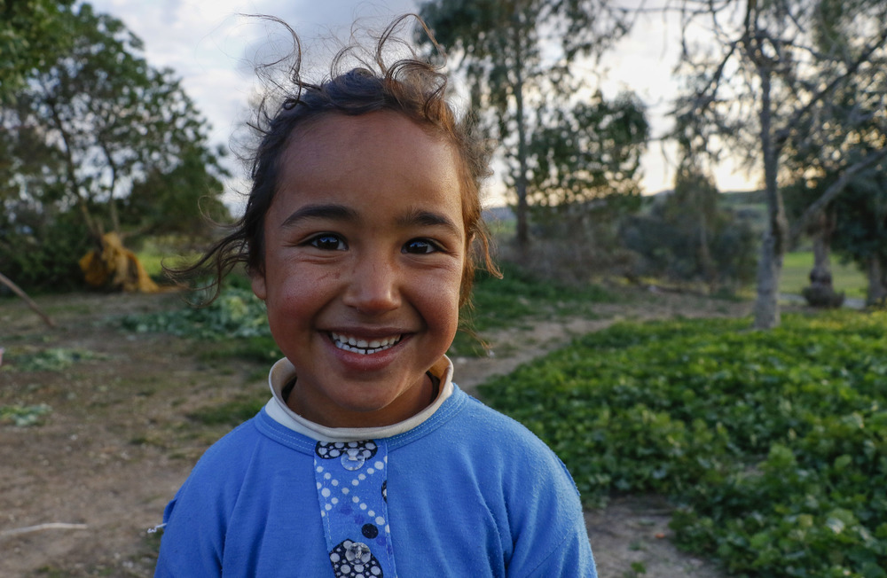 Farah, 8, is Hana's oldest child. She often stayed in her yard, waiting to be invited to play in other children's activities. Here, she poses for a photograph as her mother harvest Moroccan spinach.