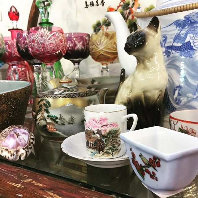 Um, so I'm in love with the colors on our #EstateSale shelf. #Antique Bohemian cut-to-clear #crystal, #vintage Asian #teacups, and a quite excellent bonus #ceramic #cat. #GardenGallery #BigSurVintage #BigSurThrift #VintageKitchen #Cheers
