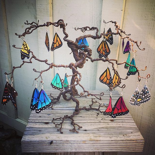 #Butterfly #earrings are back! These #handpainted #acrylic on #leather works of #WearableArt are lovingly crafted individually in #BigSur by Jill Woyt of Natural Mystic Arts. Sterling silver hooks. $50 per pair. Displayed on gorgeous handtwisted #WireArt tree by sculptor @sambonifas, $200. #GardenGalleryGirl #WearSomeArt #Wings #BigSurArt