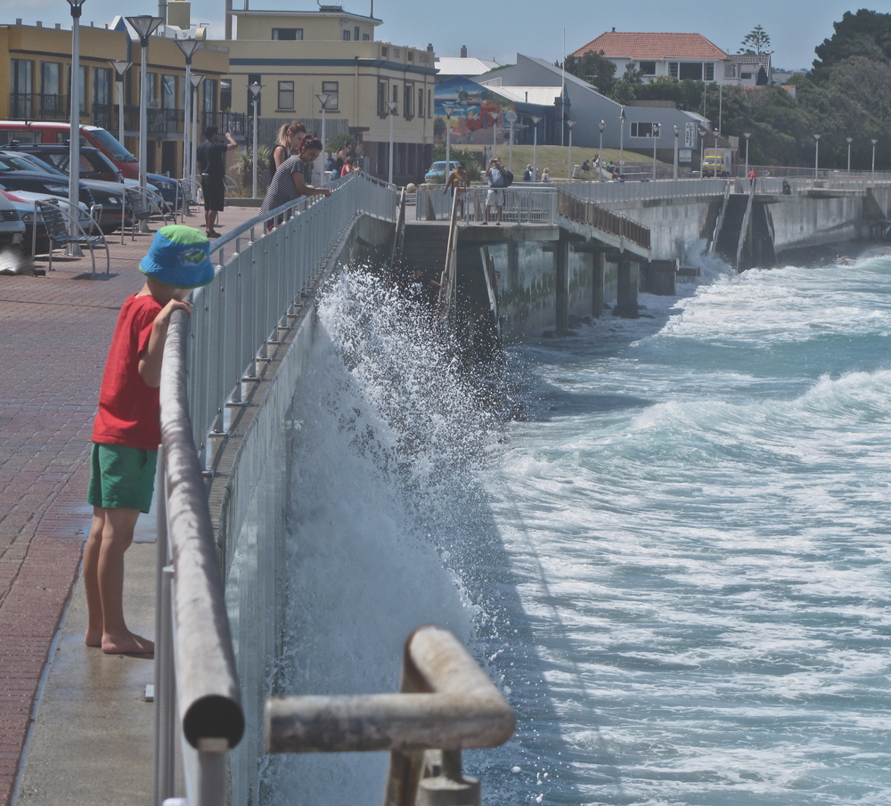 Sea Spray on esplanade St Kilda with curious child watching