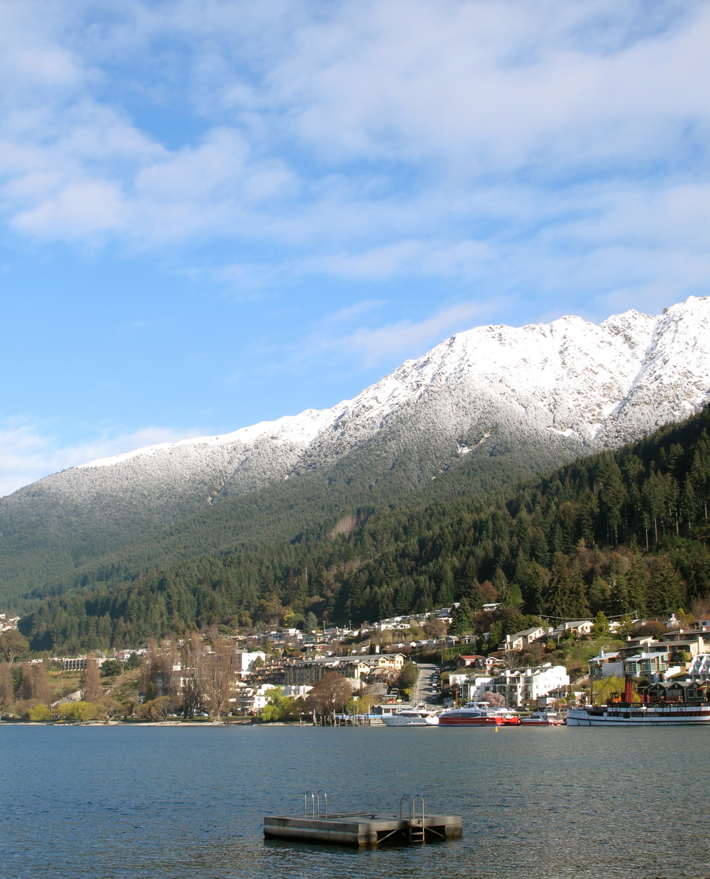 Queenstown lake and hills covered in snow and colourful houses