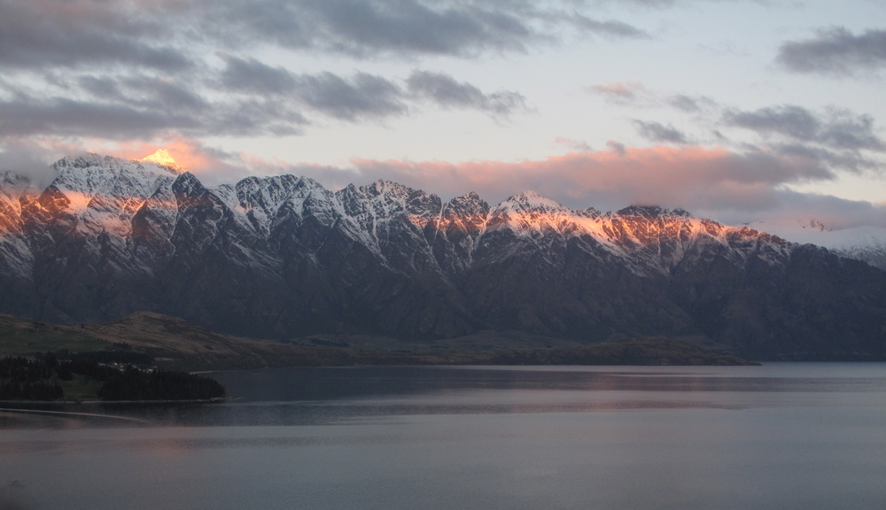 Snowcapped Queenstown mountains at dusk in pink light