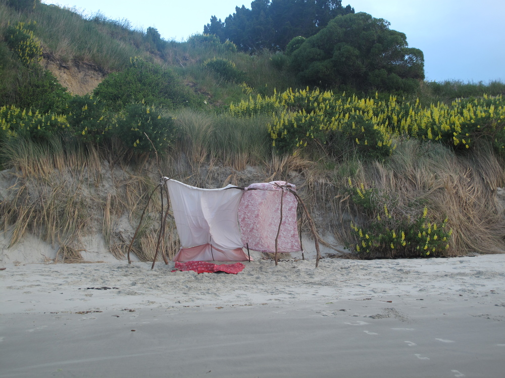 Tent fort on the beach made of branches and sheets