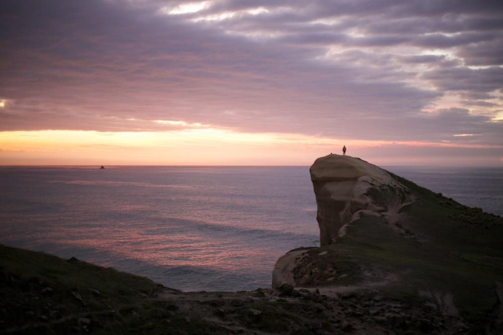Standing on the point of Tunnel Beach at sunrise, Dunedin, NZ