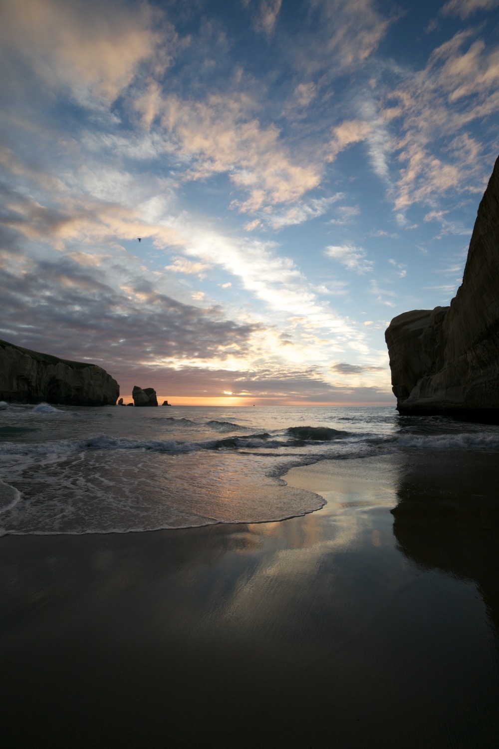 Sunrise with sea and waves and sky reflections at Tunnel Beach