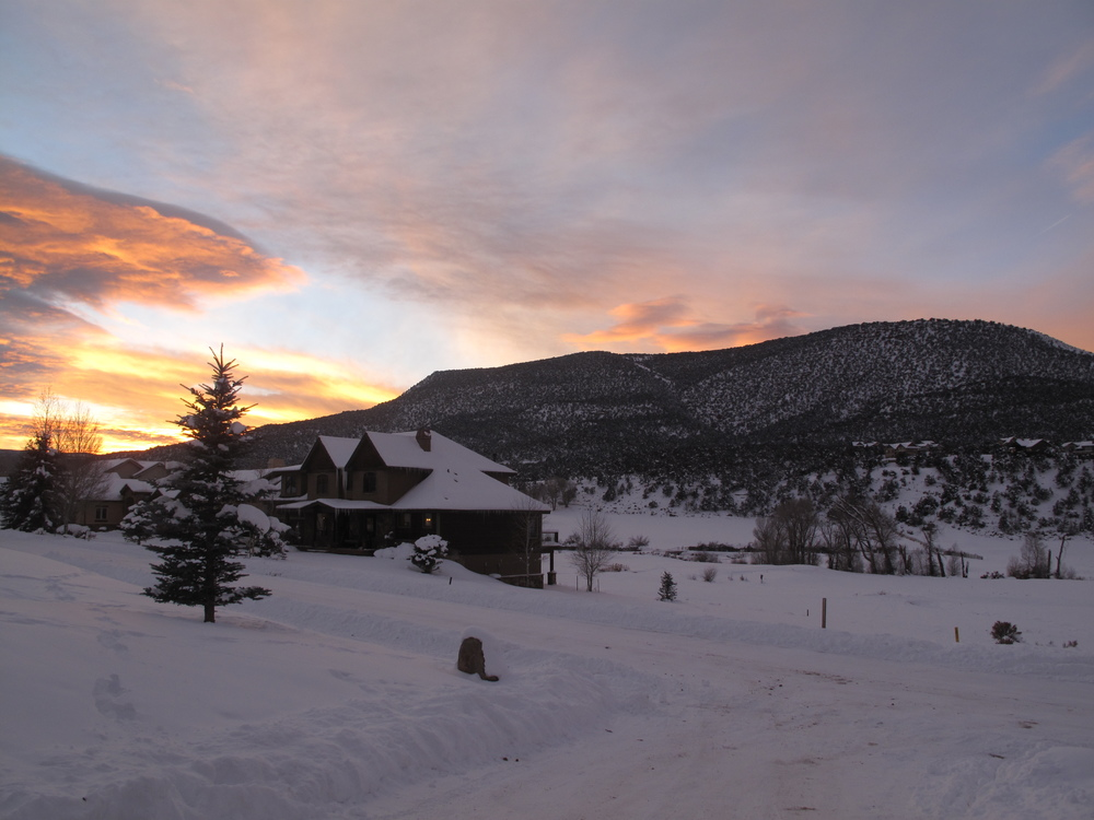 Colorado sunset in red and orange and pink, in a snowy winter village