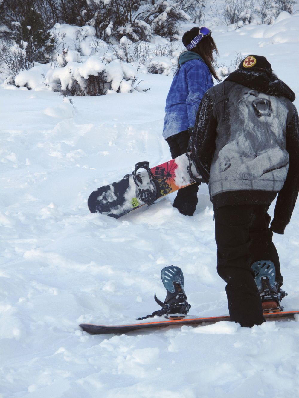 Snowboarders trekking up a snowy hill in the back country of Colorado