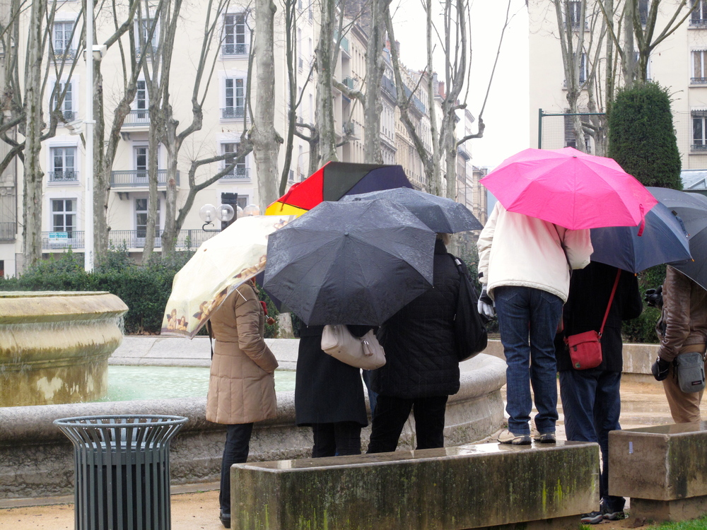 A tour group with colourful umbrellas in the rain in Lyon