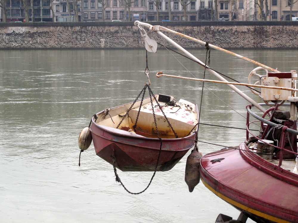 Dinghy tied to a large boat on the river in Lyon.