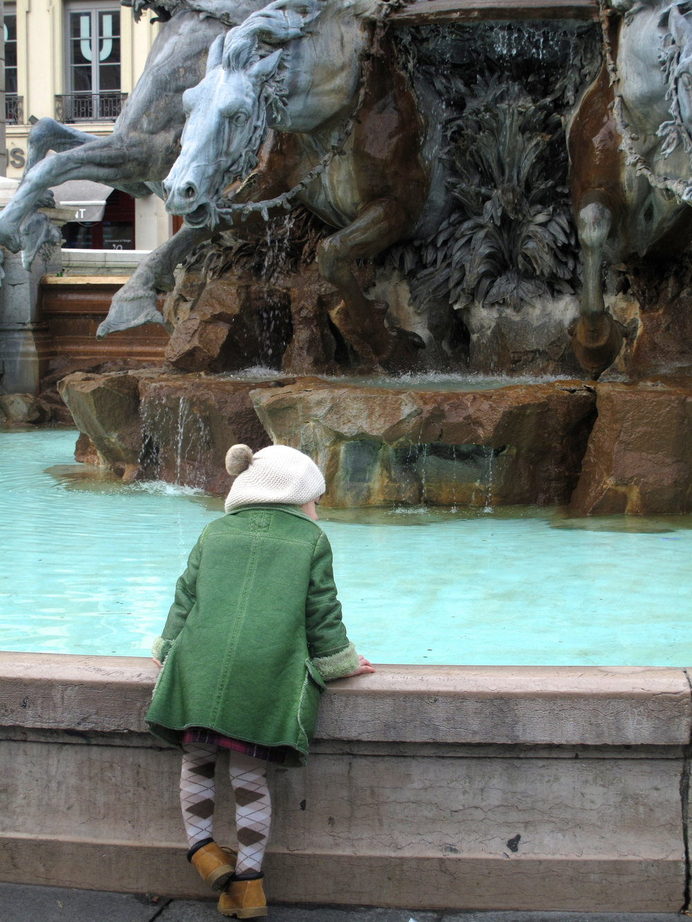 Old and young - a toddler stars into la Fontaine Bartholdi, Lyon