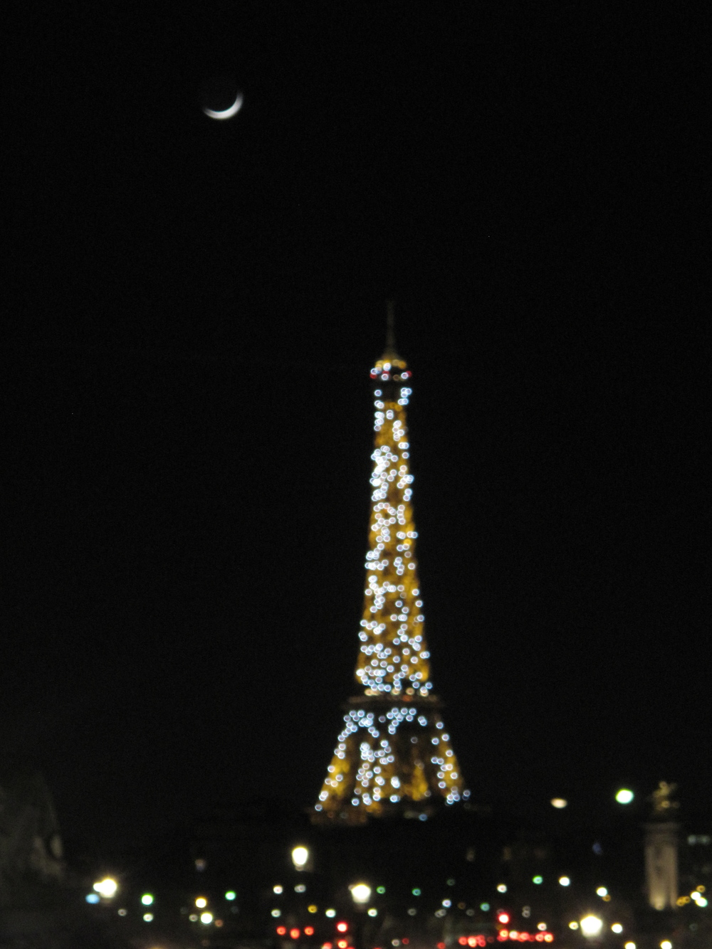 The Eiffel Tower sparkling at night under a crescent moon - blurry shot and bokeh