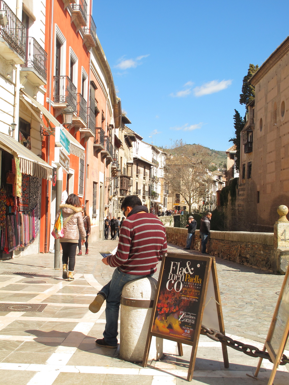A young man leaning on a post and reading the paper in the sunny streets of Granada