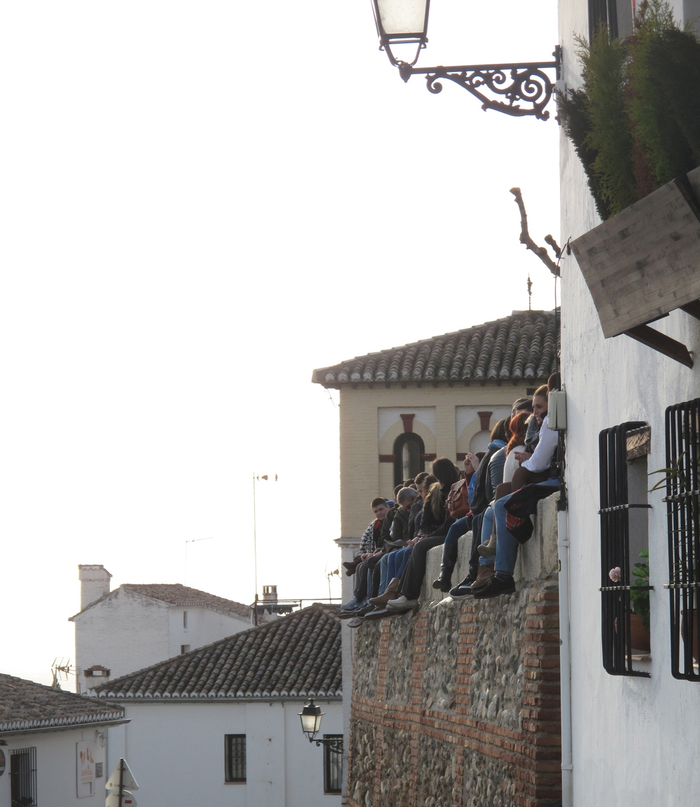 Young people sitting on a fence and watching the sunset over the Alhambra