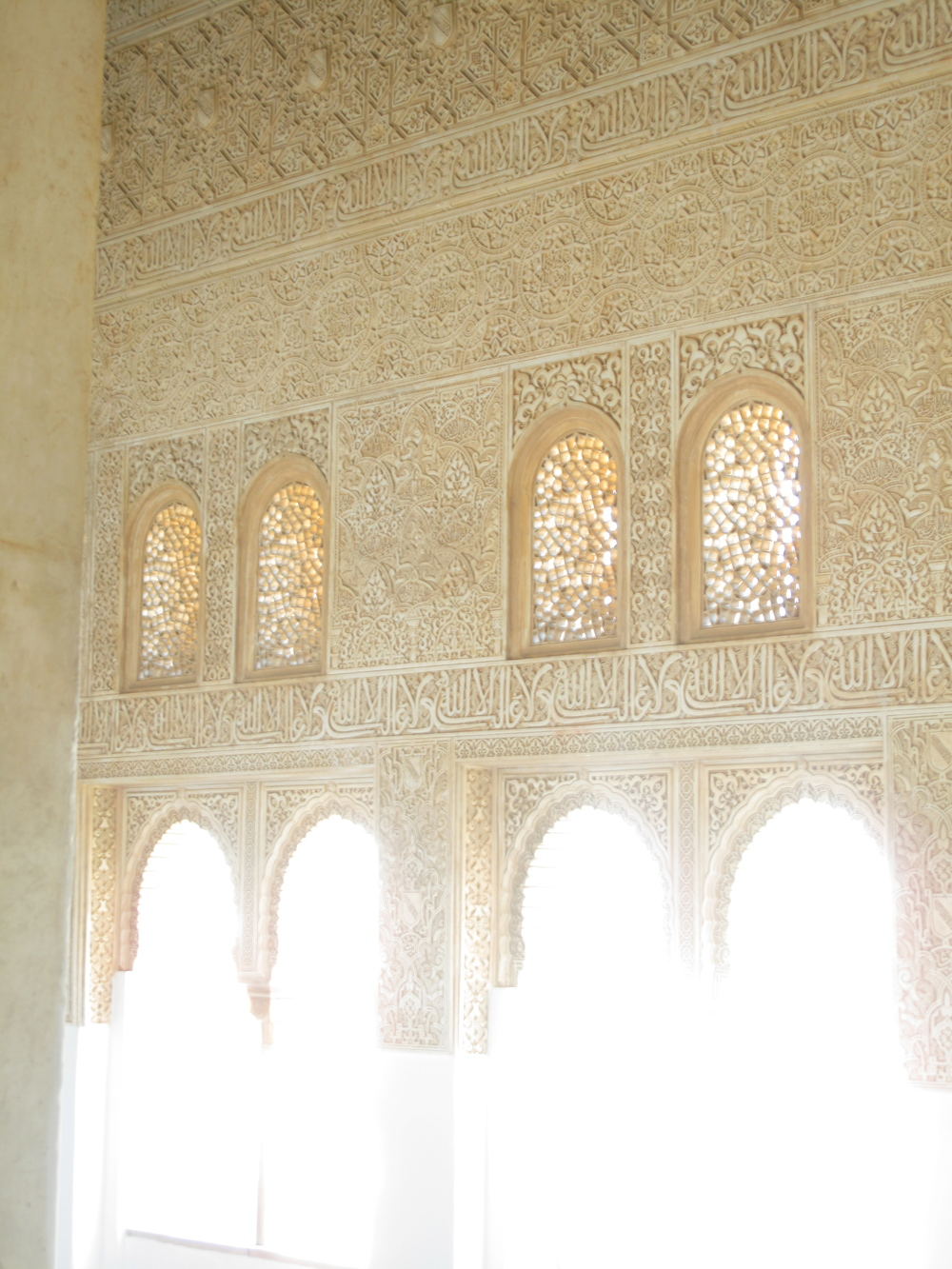 Light pouring through islamic style carvings and windows at the Alhambra