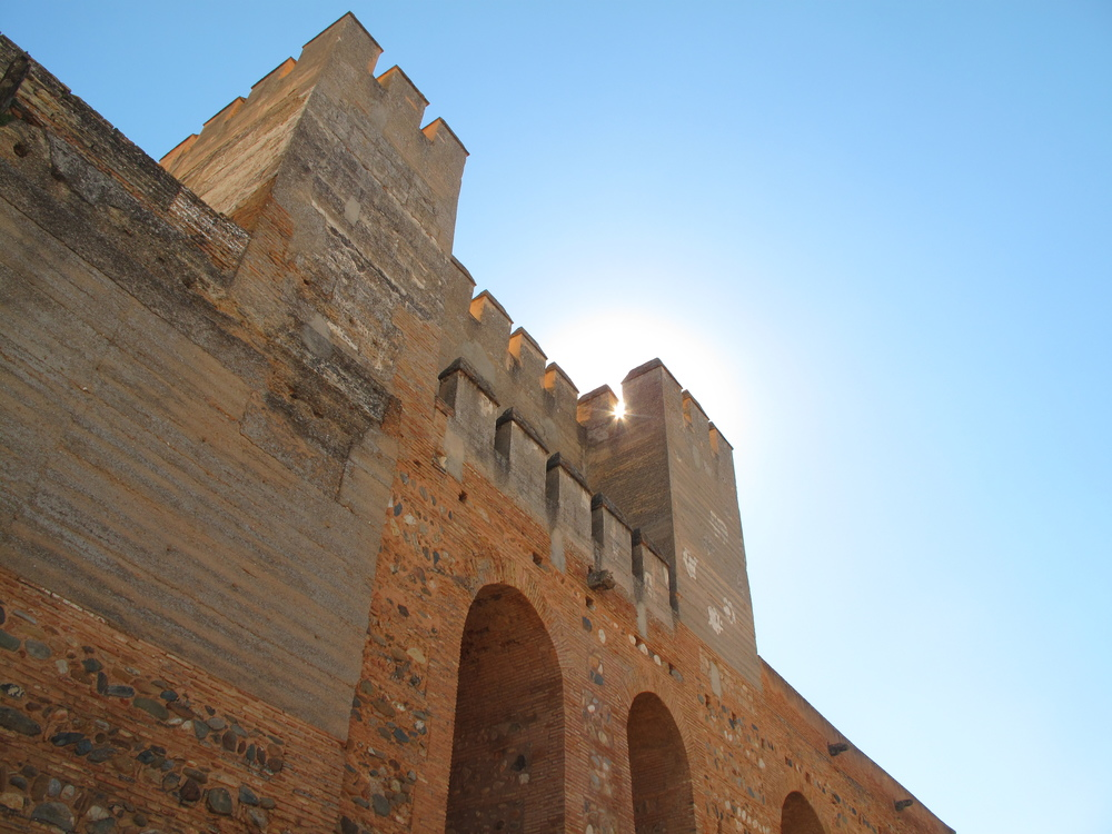 Sun stars through the crenellations of the castle at Alhambra