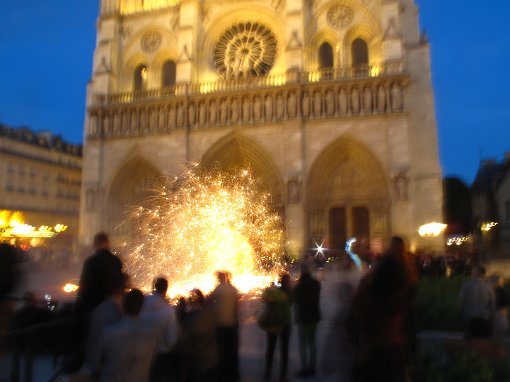 Fire performer outside the Cathedral of Notre Dame at night