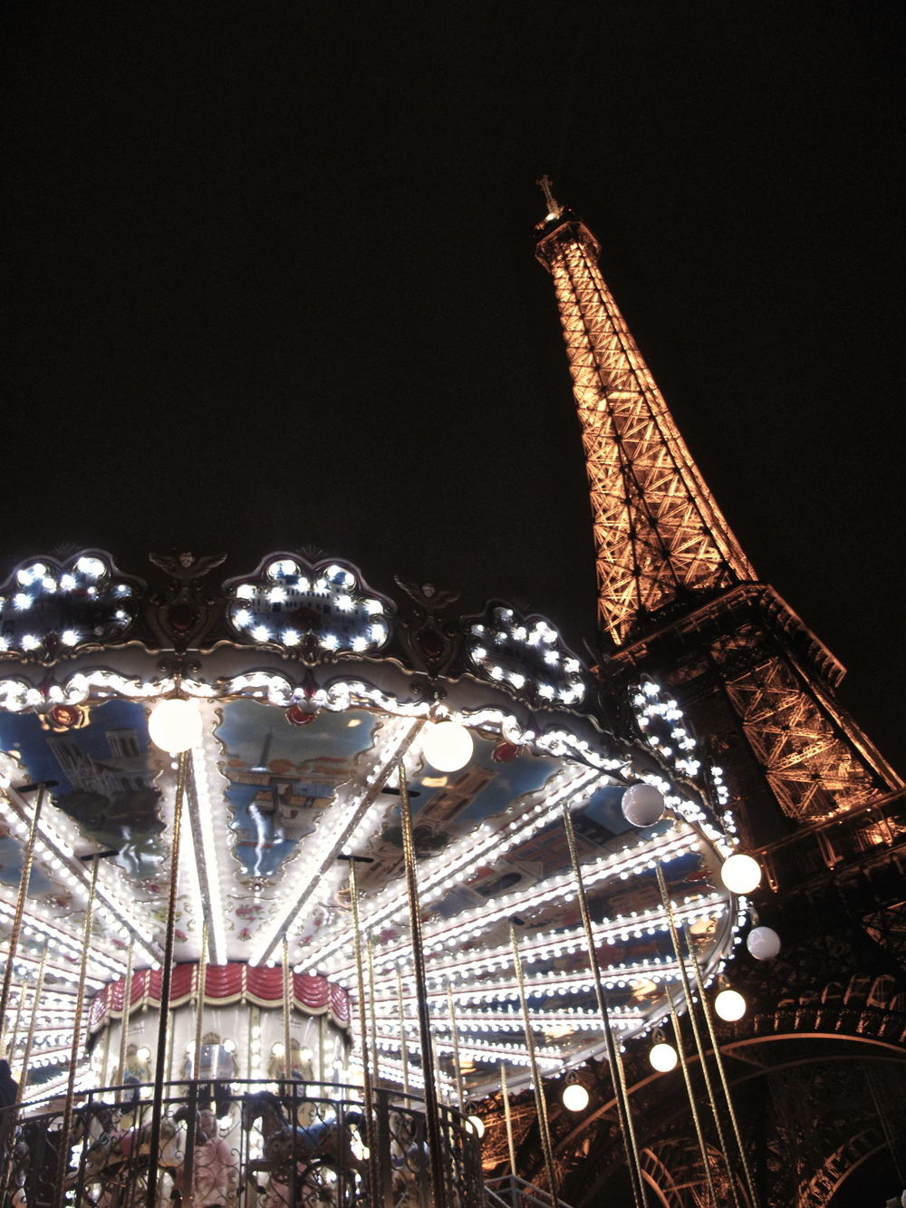 the Eiffel Tower at night lit up beside a carrousel