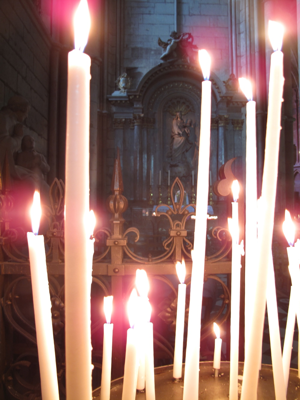Candles for prayer in the gloom of Reims Cathedral