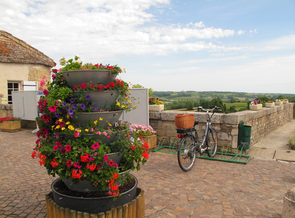 Duras - a small French village and castle on a hilltop in Bordeaux. A bunch of flowers and a bike, and magnificent views