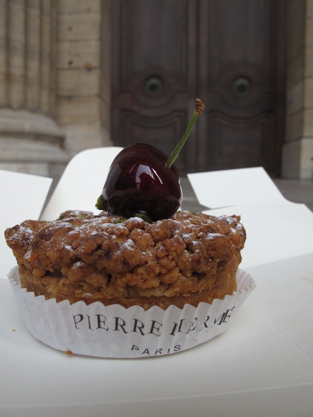 Pierre Herme pastry with cherry on top, on the steps of St Sulpice