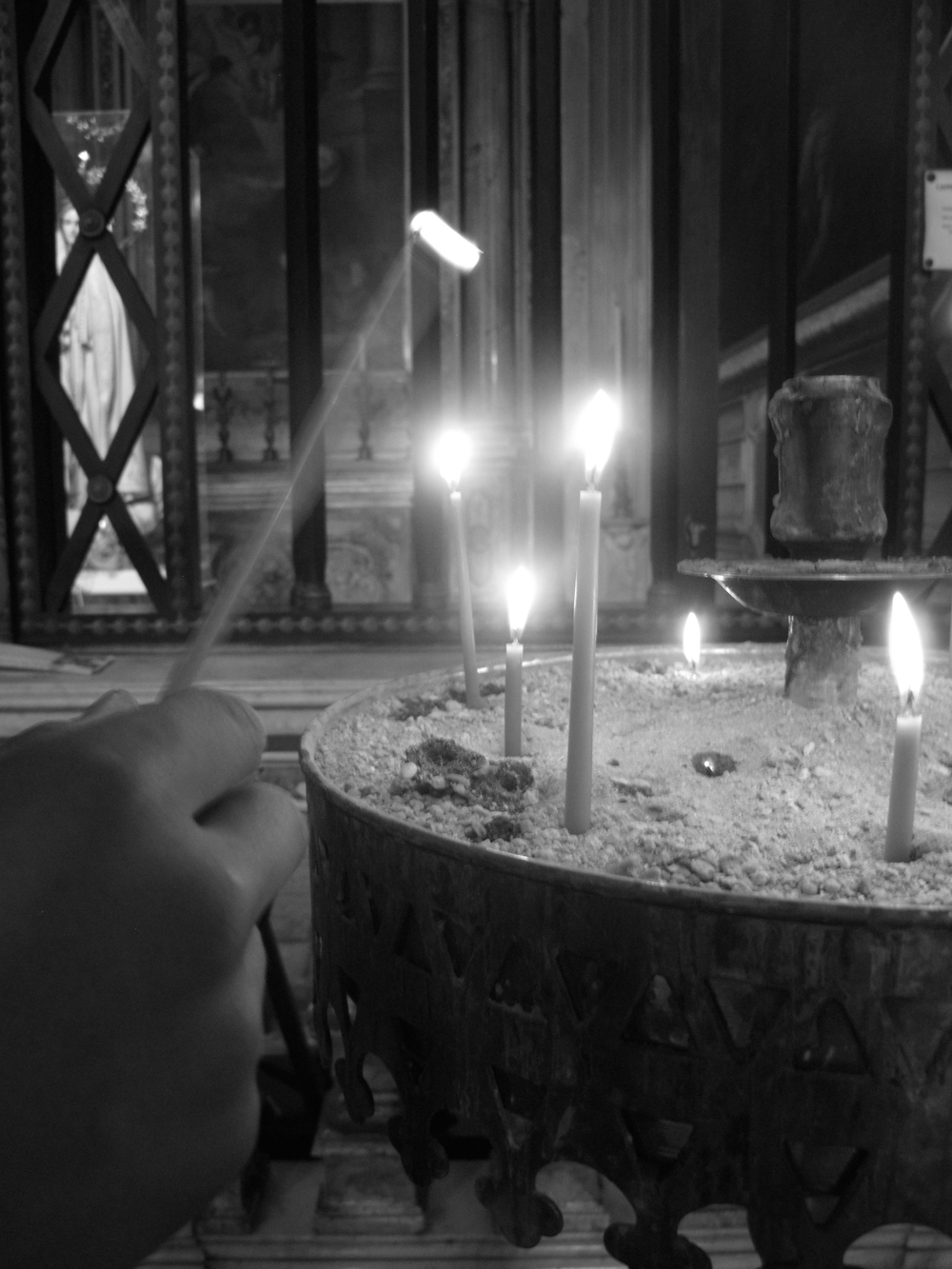 Lighting a candle in a church of Rome