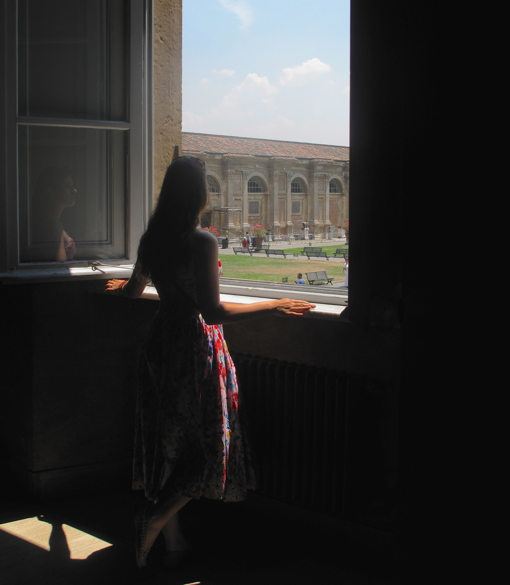 A girl looking out the window into the Vatican gardens