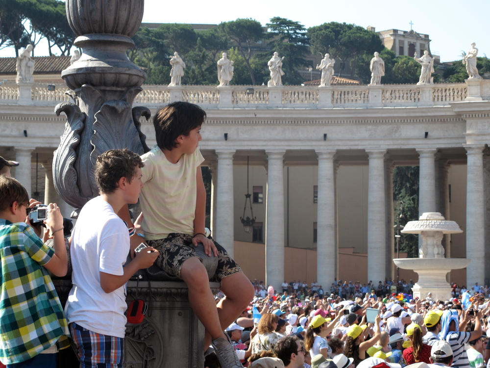 Young boys climbing a lamp post to get a look at the Pope