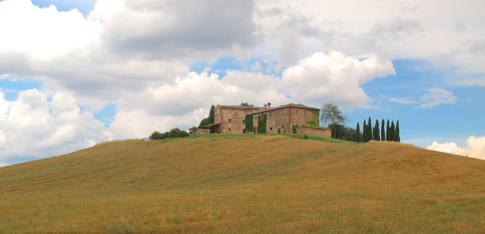 Lost in the beauty of the Tuscan countryside - with rolling hills, old stone houses, and cypress trees.