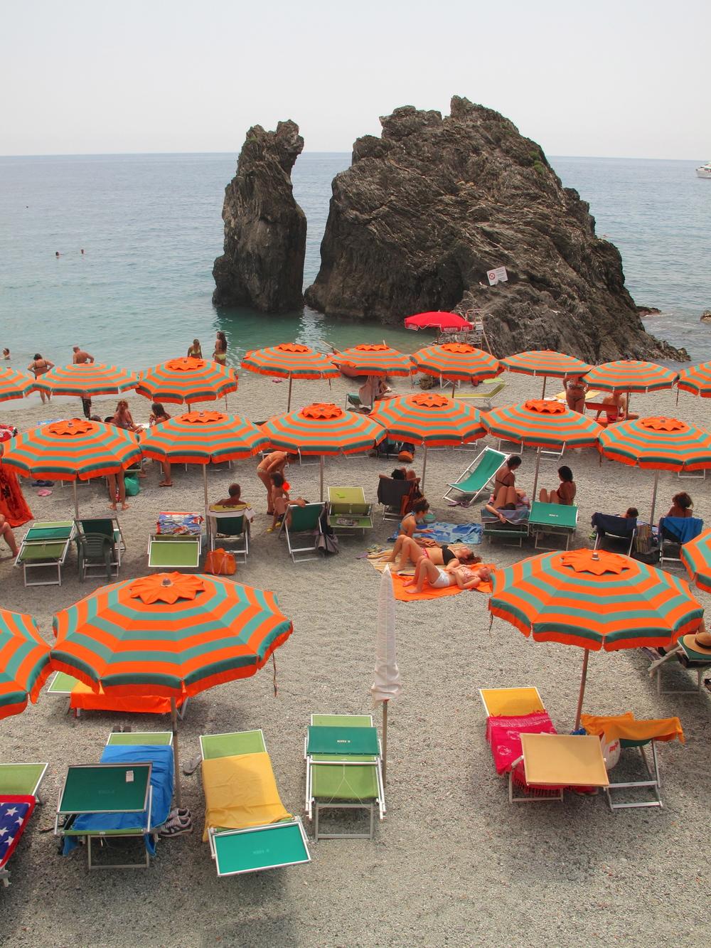 Striped orange and green sun umbrellas on the beaches of the Cinque Terre