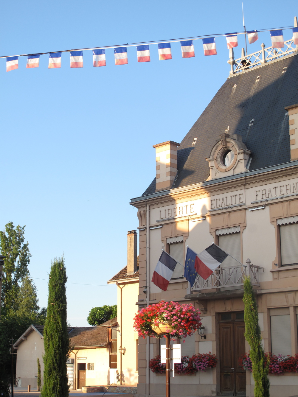 Flags and building with a sign: Liberte Egalite Fraternite, in  France