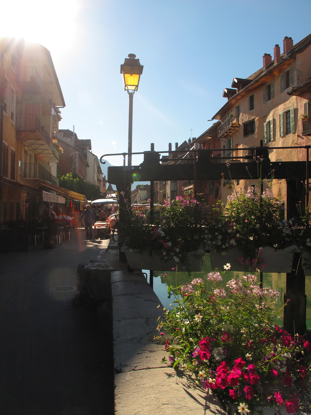 Lamp post and a bridge covered in flowers on the canals of Annecy le Vieux