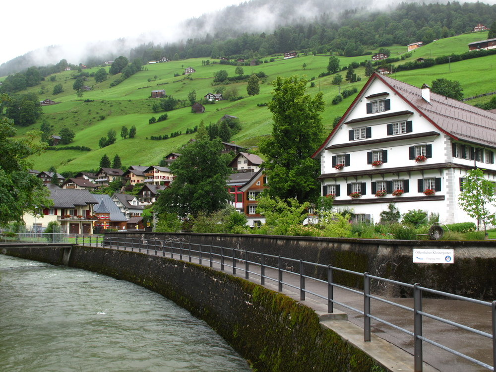 Austrian village with a river, painted houses with window shutters, and green hills.
