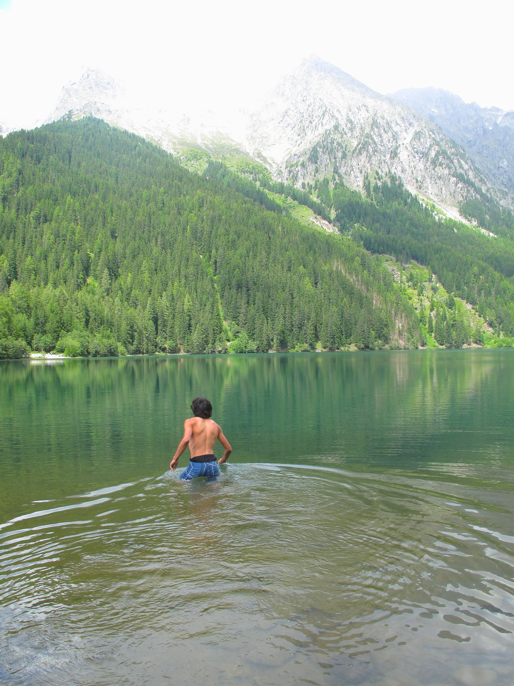 Oliver swimming in a snowmelt lake, with turquoise green waters, in Austria.