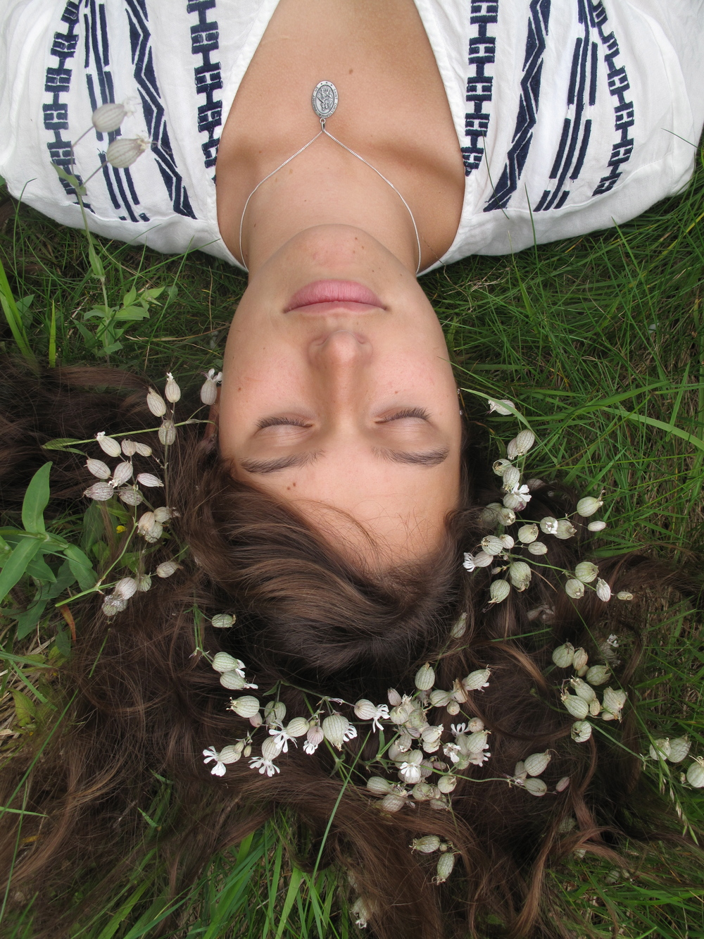 Lying in the grass with a halo of white flowers.