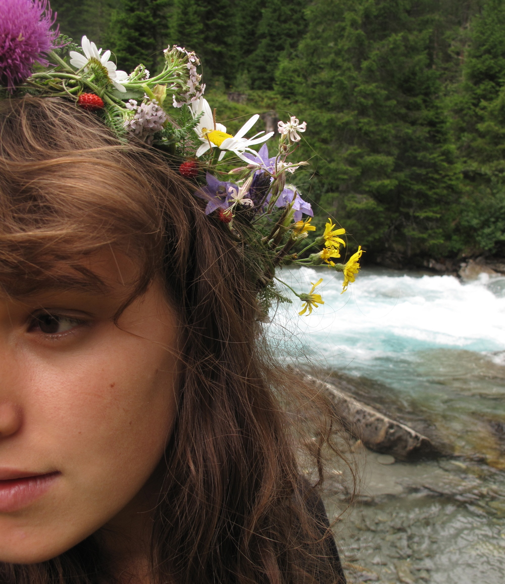 Wood nymph by the river with a flower crown of strawberries.