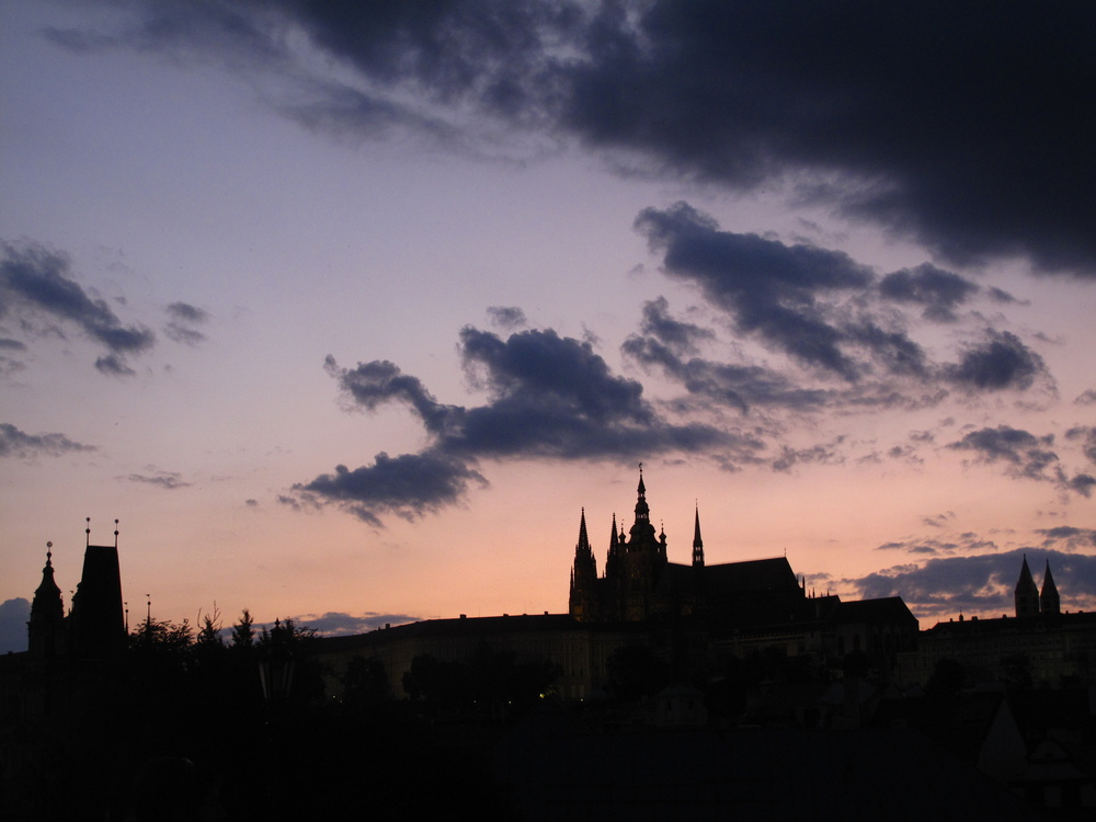 Prague castle and skyline silhouette at dusk when the sun is setting.