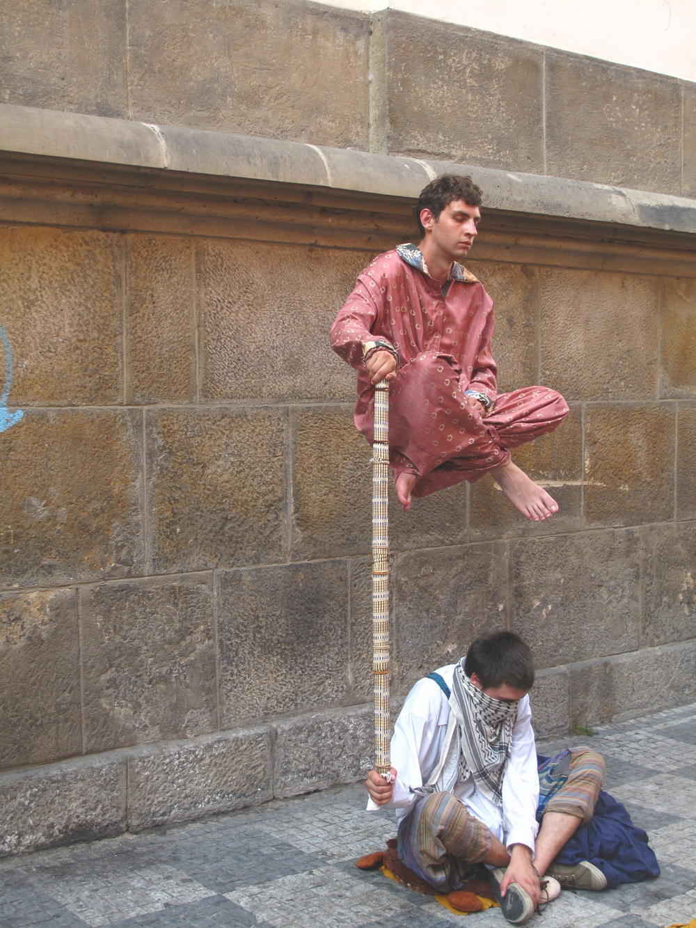 Buskers and magicians on the streets of Prague, performing levitation trick.