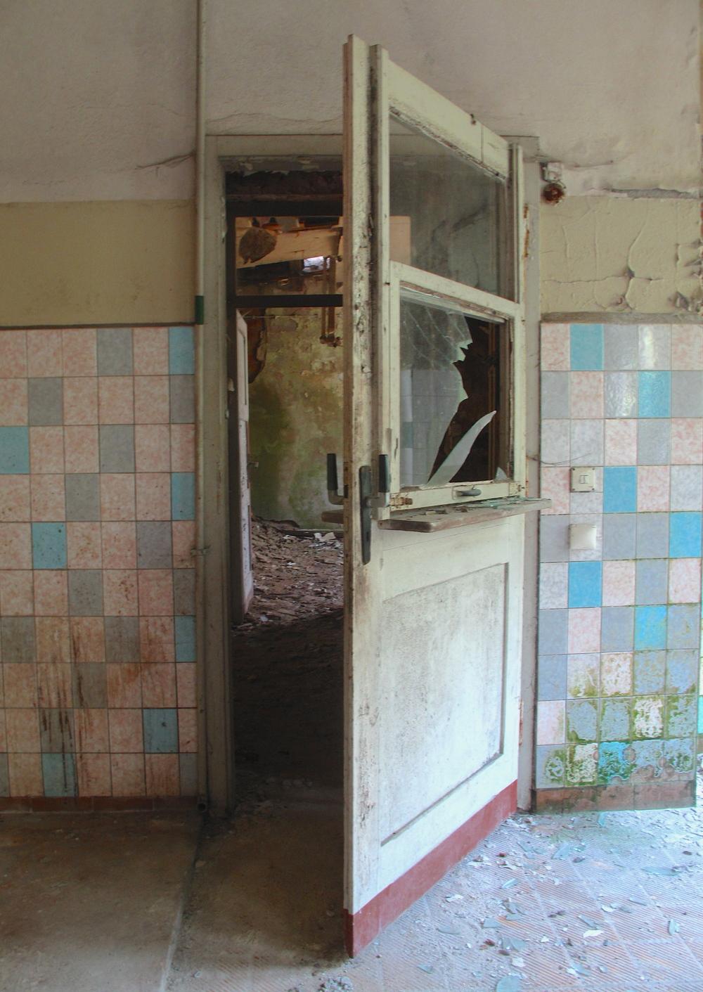 Doorway inside Elisabeth Sanatorium, with peeling wall paint and old tiles.