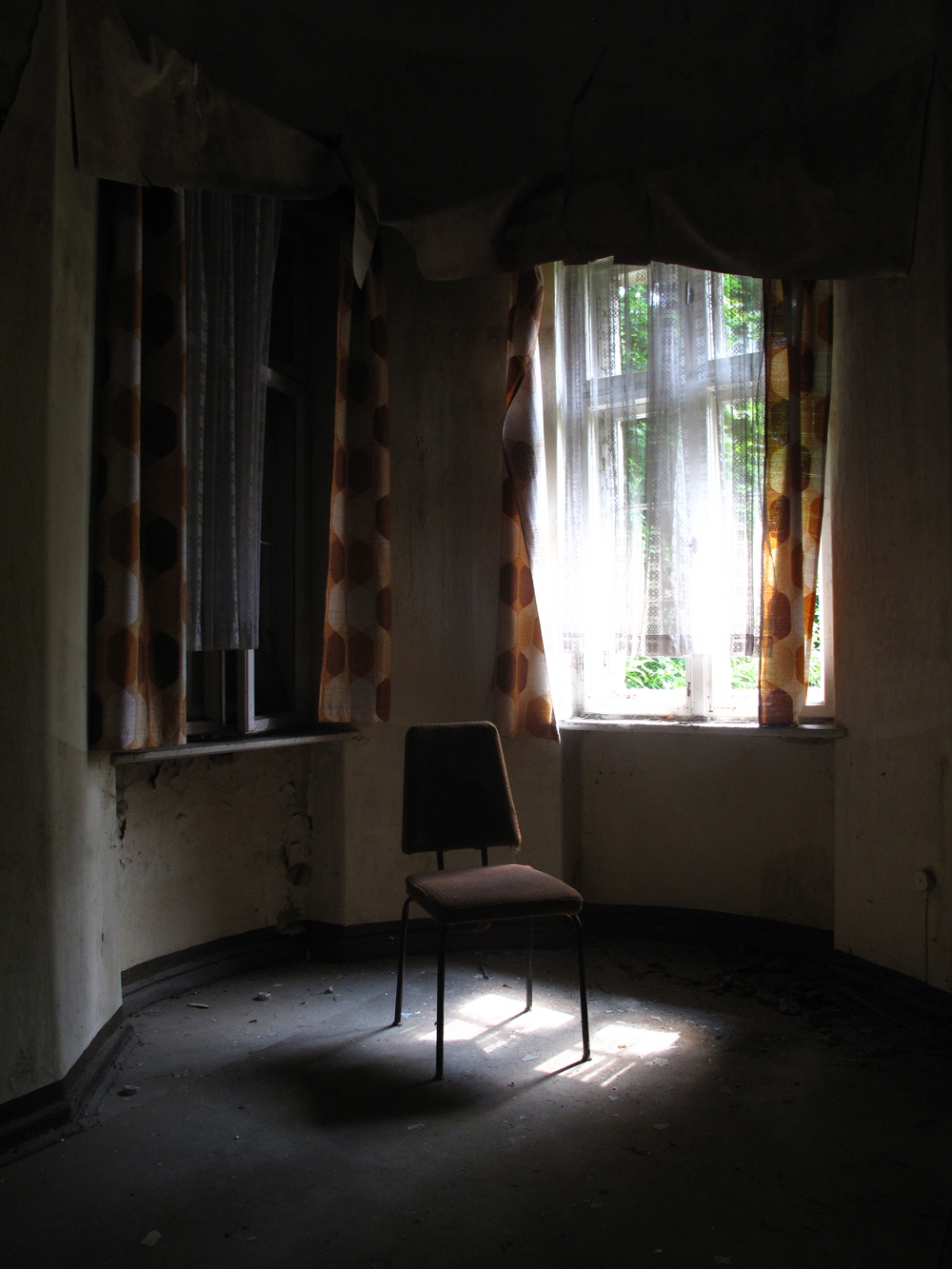 A dark room and a chair inside an abandoned sanatorium.