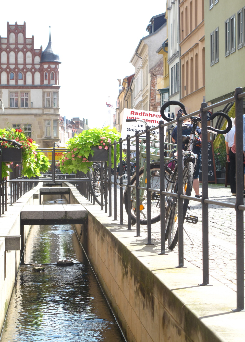 Canals through the old town of Wittenberg, with bicycles and flower baskets.