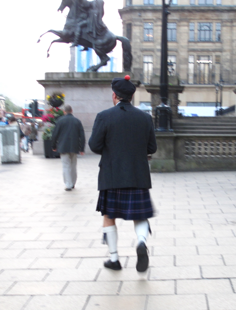 Man in traditional Scottish garb - with a pompom hat.